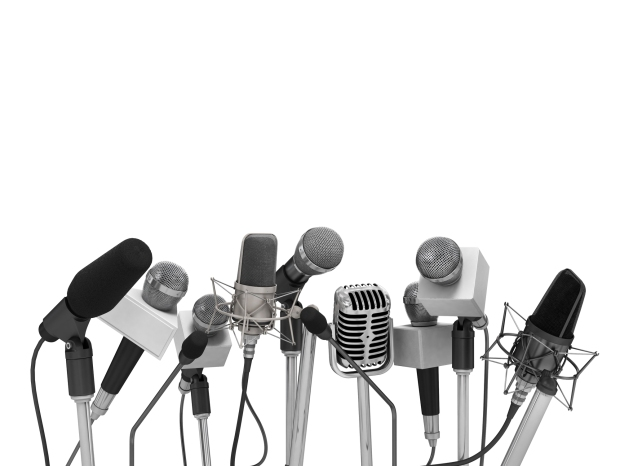 Press conference with standing microphones.